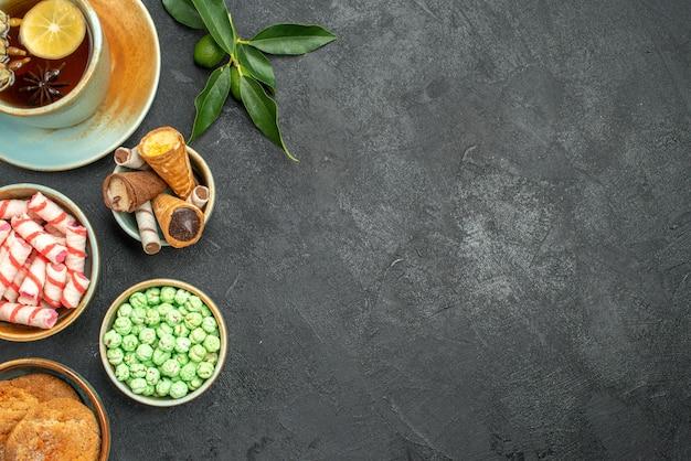 Widok z góry zbliżenie słodycze filiżanka herbaty ciasteczka wafle cukierki owoce cytrusowe