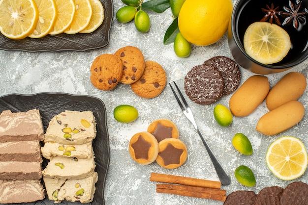 Widok z góry zbliżenie słodycze filiżanka herbaty widelec ciasteczka z pestkami słonecznika chałwa owoce cytrusowe