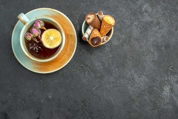 Widok z góry zbliżenie słodycze gofry w misce filiżankę herbaty ziołowej