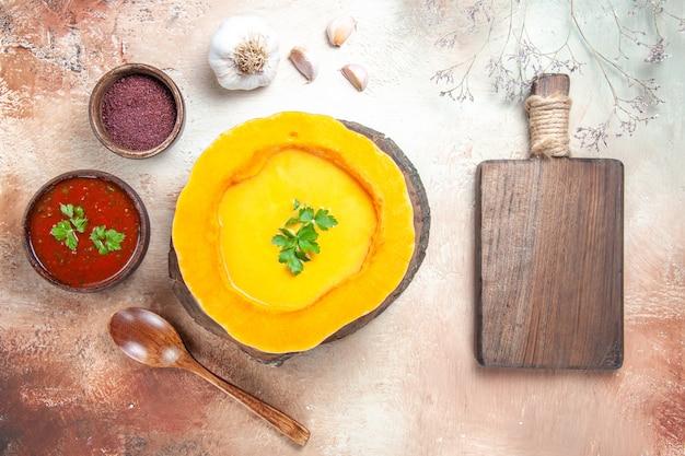 Widok z góry zbliżenie zupa czosnek łyżka sos przyprawy zupa dyniowa obok deski do krojenia