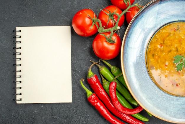 Widok z góry zbliżenie zupa z soczewicy zupa z soczewicy ostra papryka pomidory z szypułkami biały notatnik