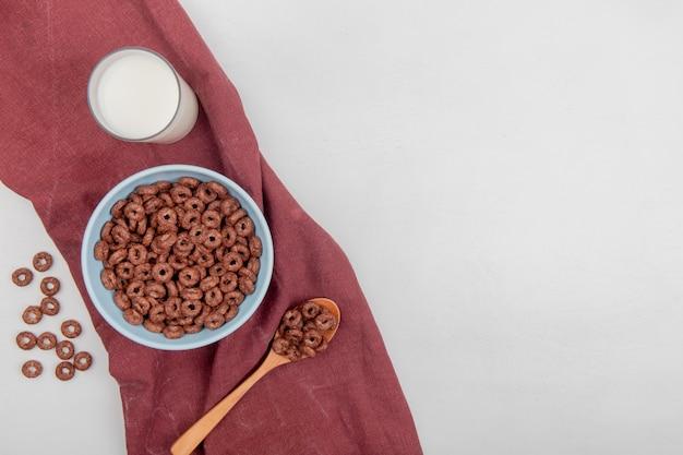 Widok z góry zbóż w misce i drewnianą łyżką z mlekiem na tkaninie bordo i białym tle z miejsca kopiowania