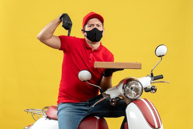 Widok z góry zdezorientowanego kuriera w czerwonej bluzce i rękawiczkach w masce medycznej siedzi na skuterze skierowanym w dół i pokazując porządek