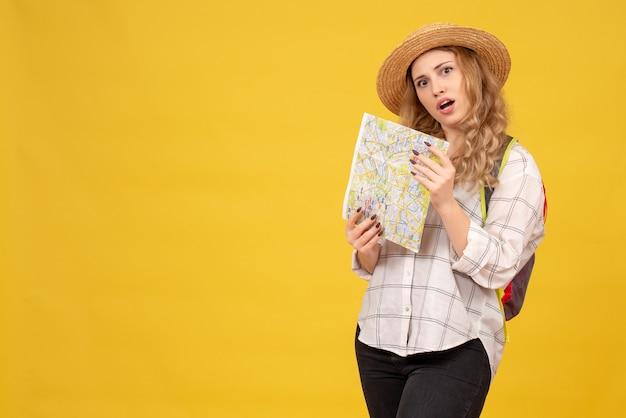 Widok z góry zdezorientowanej dziewczyny w podróży w kapeluszu i plecaku trzymając mapę na żółto