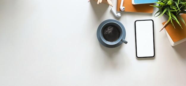 Widok z góry zdjęcia filiżanki gorącej kawy na białym biurku i otoczonej białym smartfonem z pustym ekranem, bezprzewodowymi słuchawkami, notatnikiem, pamiętnikiem, rośliną doniczkową i uchwytem na ołówek.
