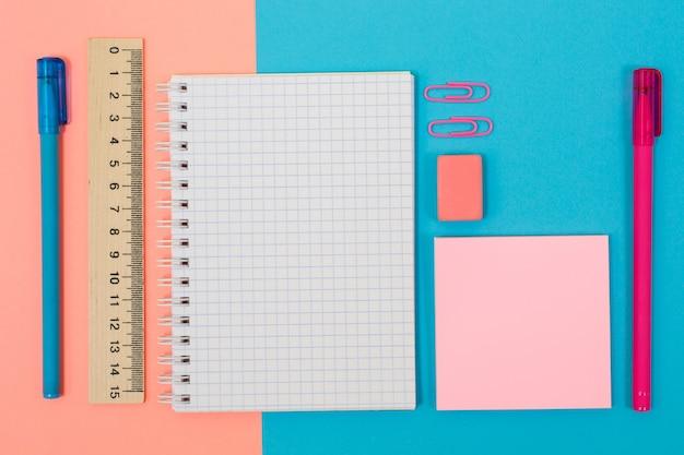 Widok z góry zdjęcie jasnych i kolorowych papeterii. zestaw spiralnych notatników, długopisów, gumki, linijki, naklejek i klipsów na pół niebieskim, pół różowym tle