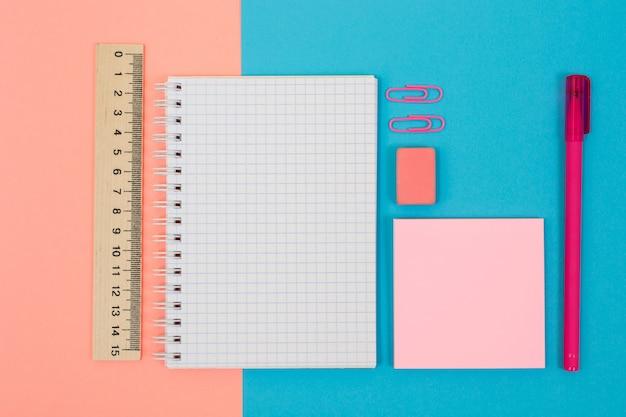 Widok z góry zdjęcie jasnych i kolorowych przyborów szkolnych. zestaw spiralnego notatnika, długopisu, gumki, linijki, naklejek i klipsów na pół niebieskim, pół różowym tle