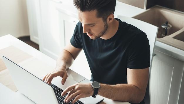 Widok z góry zdjęcie kaukaskiego mężczyzny piszącego na komputerze podczas pracy w domu