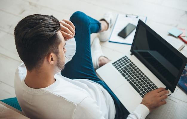 Widok z góry zdjęcie kaukaskiego mężczyzny trzymającego laptop i myślącego podczas pracy z niektórymi dokumentami