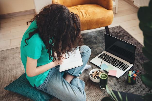 Widok z góry zdjęcie kaukaskiego ucznia odrabiającego lekcje na podłodze i używającego laptopa podczas jedzenia płatków z sokiem warzywnym
