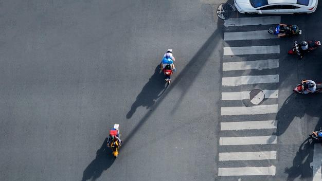 Widok z góry zdjęcie lotnicze motocykla jazdy przechodzi przejście dla pieszych w ruchu drogowego z sylwetka światła i cienia.
