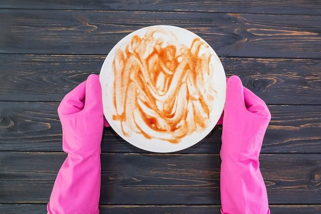 Widok z góry zdjęcie rąk w różowych gumowych rękawiczkach trzymających brudny talerz na drewnianym tle
