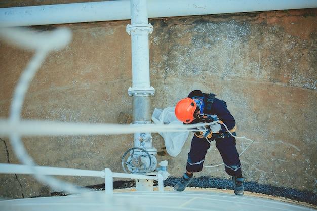Widok z góry zdjęcie spawacza przemysłowego z dostępem linowym, pracującego na wysokości, noszącego uprząż, sprzęt zabezpieczający kask, kontrola dostępu linowego w przemyśle zbiorników o grubości.