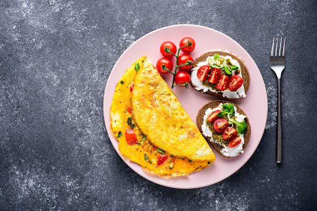 Widok z góry zdrowe śniadanie składające się z omletu jajecznego, pełnoziarnistych tostów z twarogiem, pesto i pomidorkami koktajlowymi na różowym talerzu na czarnym kamiennym tle z kopią miejsca.
