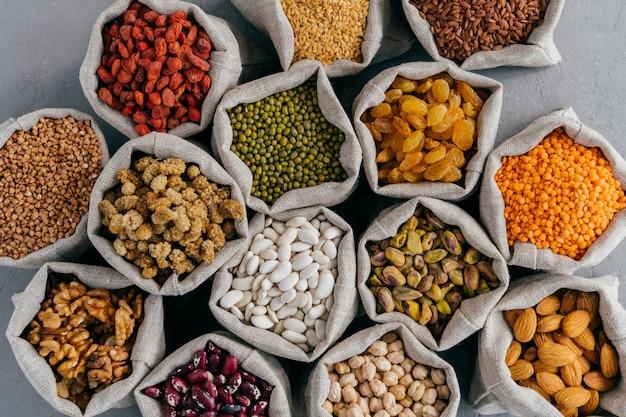 Widok z góry zdrowych suchych składników w workach jutowych. pożywne płatki zbożowe i suszone owoce: migdał, garbanzo, pistacja, goji, kasza gryczana, morwa, rośliny strączkowe w workach z tkaniny