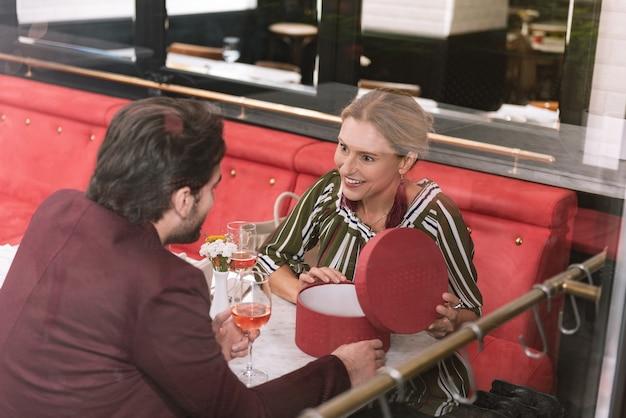 Widok z góry zdumiony szczęśliwą kobietą otwierającą prezent i mężczyzna pije wino