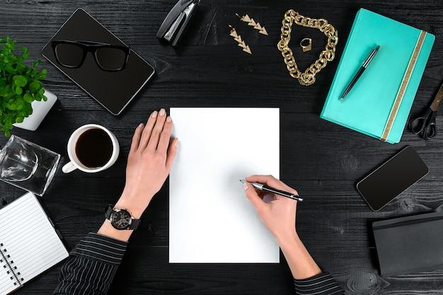 Widok z góry ze stołem biurowym w przestrzeni kopii, notatnikiem z filiżanką kawy i smartfonem