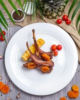 Widok z góry żeberka jagnięce z grilla z bakłażanem pomidory czereśniowe suszone morele na talerzu