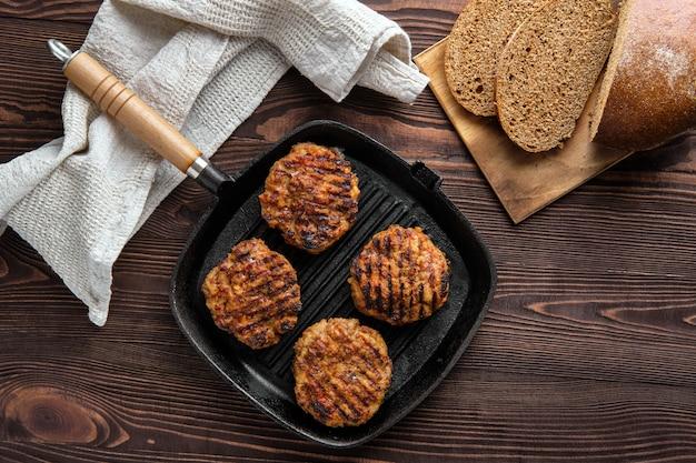 Widok z góry żeliwnej patelni grillowej z kotletami wołowymi i świeżo upieczonym brązowym chlebem