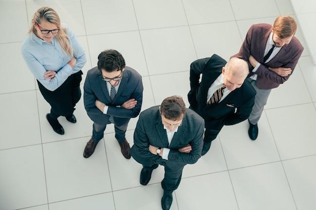 Widok z góry. zespół pewnych siebie profesjonalistów stojących w biurze