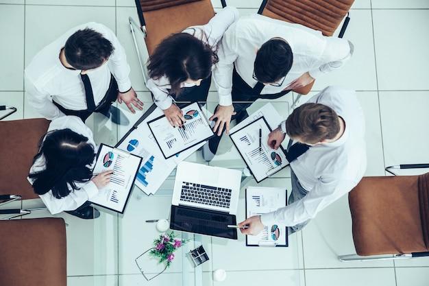 Widok z góry zespołu biznesowego omawiającego plan finansowy firmy dotyczący nowoczesnego miejsca pracy