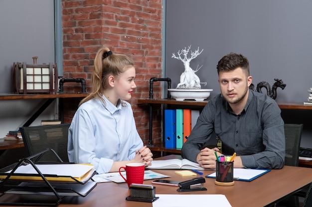 Widok z góry zespołu zarządzającego biurem siedzącego przy stole omawiającego jeden temat w biurze