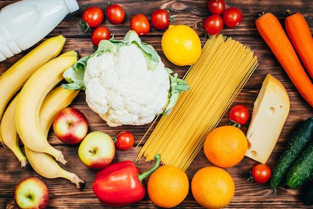 Widok z góry zestaw żywności warzywa owoce nabiał na drewnianych