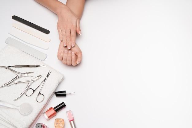 Widok z góry zestawu narzędzi do pielęgnacji paznokci na jasnych powierzchniach - szczoteczka, nożyczki, lakier do paznokci, pilnik i pęseta
