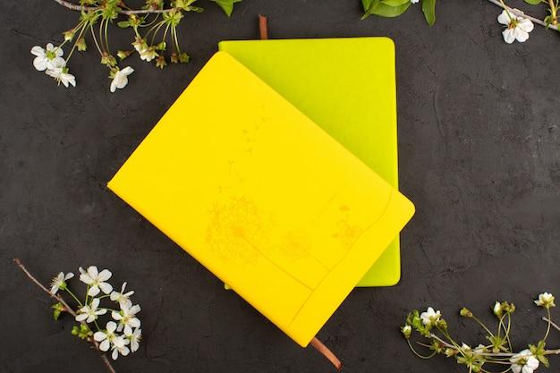 Widok z góry zeszyty żółte i musztardowe kolorowe wokół białych kwiatów na ciemnej podłodze