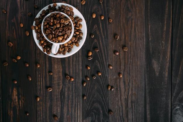 Widok z góry ziaren kawy w białej filiżance kawy espresso na prosty drewniany stół