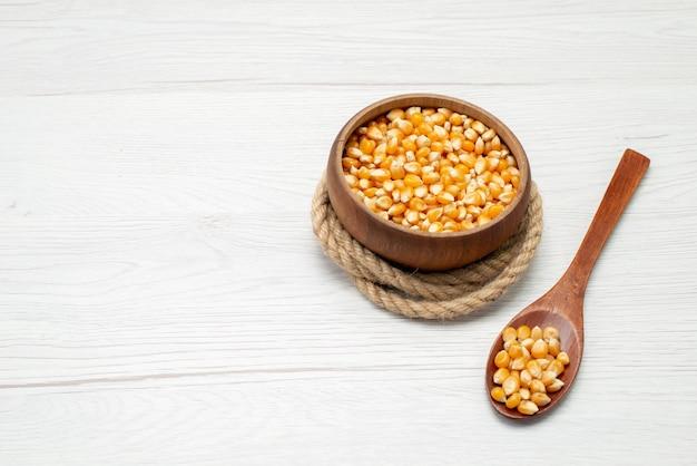 Widok z góry ziarna kukurydzy w kolorze żółtym z drewnianą łyżką na białym tle
