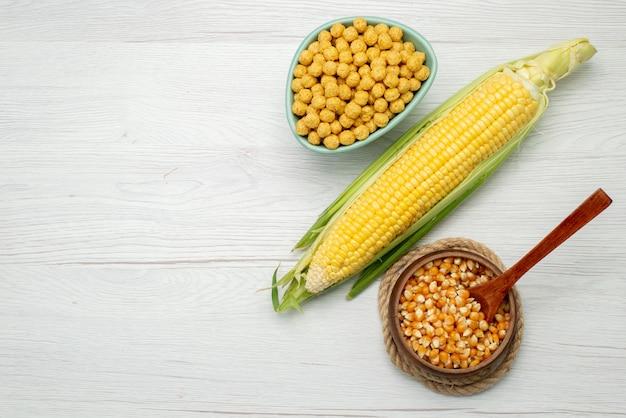 Widok z góry ziarna kukurydzy w kolorze żółtym ze zbożami wewnątrz płyty na białym tle