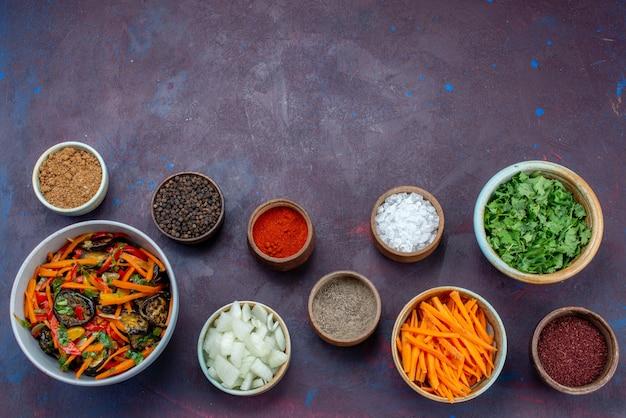 Widok z góry zieleniny i przyprawy z pokrojoną cebulą i sałatką warzywną na ciemnym biurku sałatka jedzenie posiłek przekąska warzywna