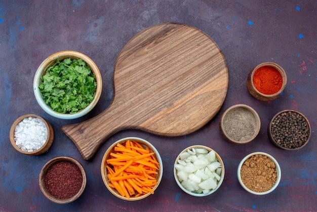 Widok z góry zieleniny i przyprawy z pokrojoną cebulą na ciemnym biurku sałatka jedzenie posiłek przekąska warzywna