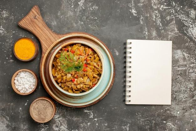 Widok z góry zielona fasolka z pomidorami biały notatnik obok tablicy z talerzem zielonej fasoli i trzema przyprawami