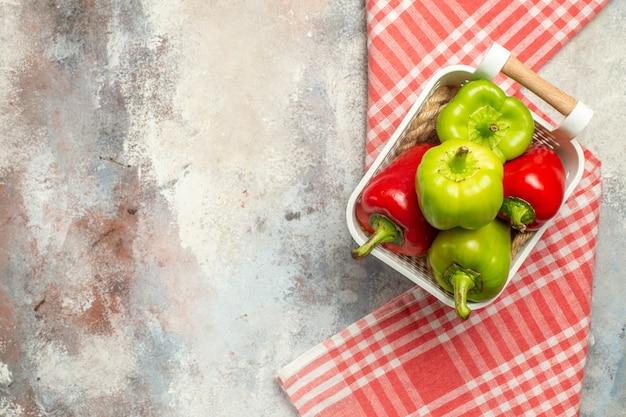 Widok z góry zielona i czerwona papryka w plastikowym koszu czerwony biały obrus w kratkę na nagiej powierzchni z wolną przestrzenią