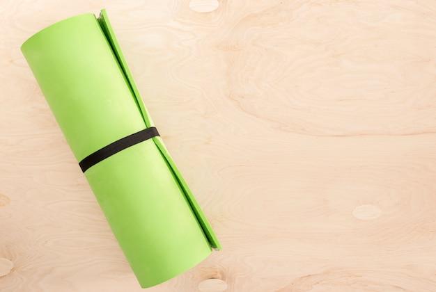 Widok z góry zielona mata do jogi lub aktywność sportowa na drewnianych
