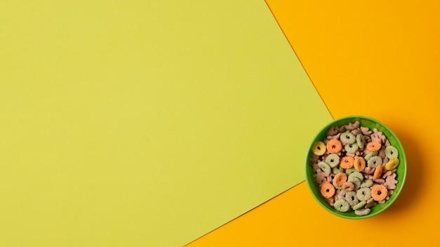 Widok z góry zielona miska z kolorowymi płatkami