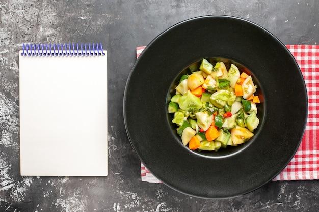 Widok z góry zielona sałatka z pomidorów na owalnym notatniku talerzowym na ciemnym tle