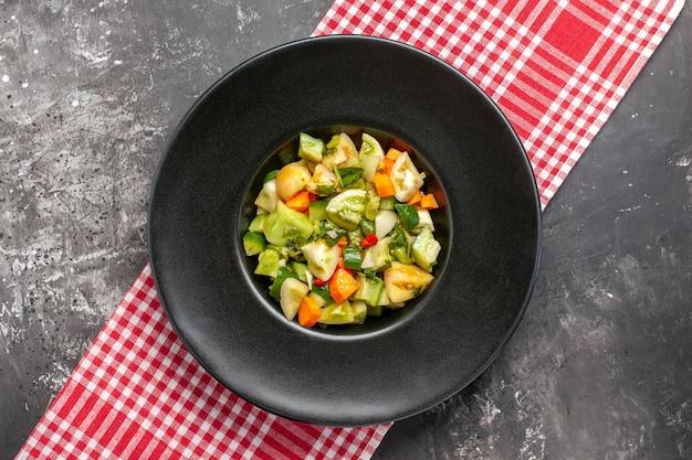Widok z góry zielona sałatka z pomidorów na owalnym talerzu na obrusie na ciemnym tle