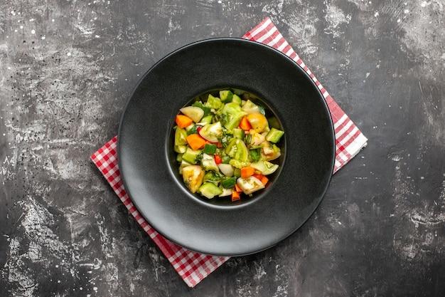 Widok z góry zielona sałatka z pomidorów na owalnym talerzu na serwetce na ciemnym tle