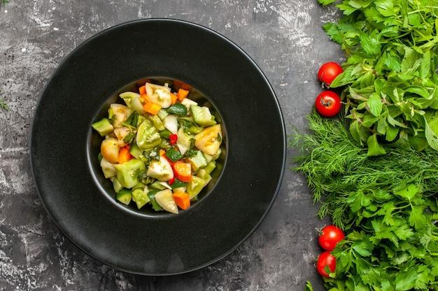 Widok z góry zielona sałatka z pomidorów na owalnym talerzu zielonych pomidorów na ciemnym tle