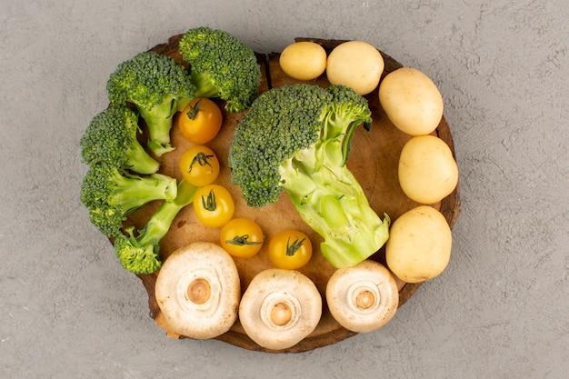 Widok z góry zielone grzyby brokuł wraz z żółtymi pomidorami i ziemniakami na szarej podłodze