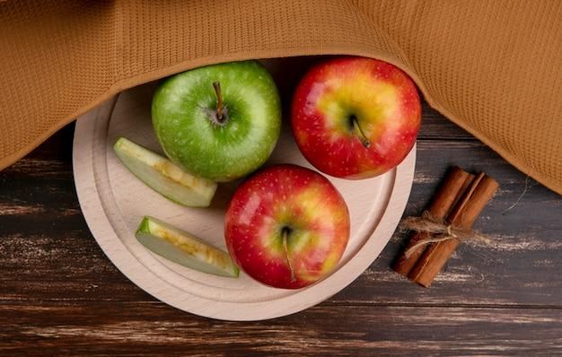 Widok z góry zielone i czerwone jabłka na stojaku z cynamonem i brązowy ręcznik na drewnianym tle