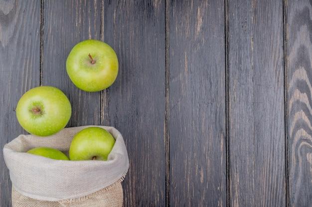 Widok z góry zielone jabłka wycieki z worka na drewniane tła z miejsca kopiowania