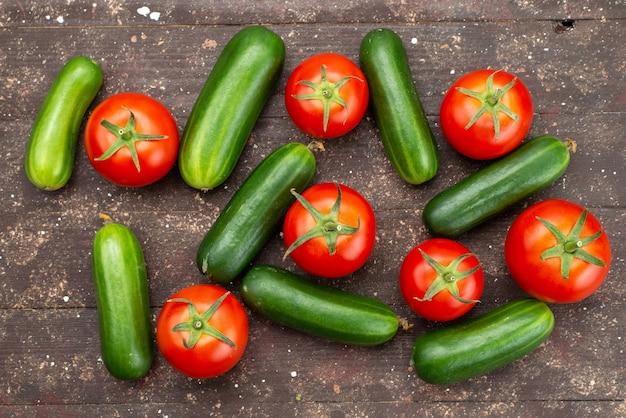 Widok z góry zielone ogórki świeże i dojrzałe z czerwonymi pomidorami na brązowym, warzywnym pokarmie z drzewa roślinnego