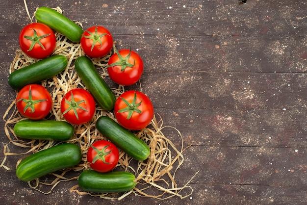Widok z góry zielone ogórki świeże i dojrzałe z pomidorami na brązowym, warzywnym pokarmie z drzewa roślinnego