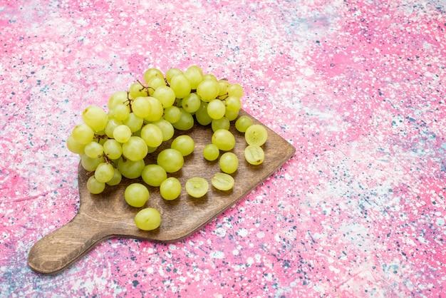 Widok z góry zielone winogrona świeże łagodne i soczyste owoce na jasnej powierzchni owoce łagodne soczyste fioletowe