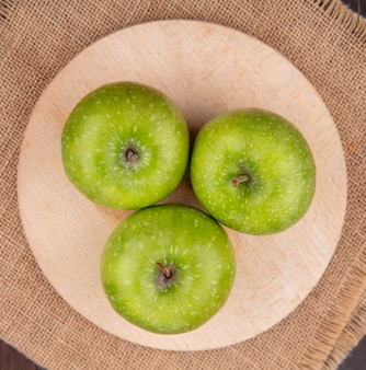 Widok z góry zielonych i świeżych jabłek na drewnianej desce kuchennej na powierzchni tkaniny worek