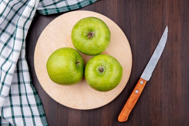 Widok z góry zielonych i świeżych jabłek na drewnianej desce kuchennej z nożem z szmatką w kratkę na drewnianej powierzchni